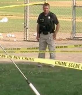 police officer stands behind crime scene tape
