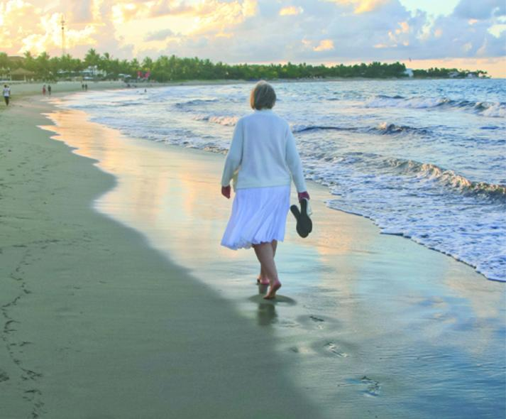 older woman walking on the beach