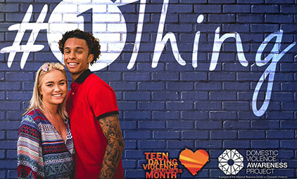 teens stand in front of blue wall with #1Thing logo