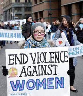 person holding sign that says end violence against women