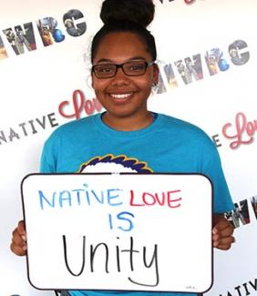 Tanae LeClare holding up sign that says Native love is unity