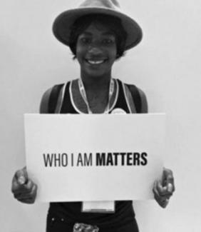 "Legacee Medina holding sign that says ""who I am matters"""
