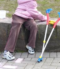 A photo of a person from the shoulders down. They are sitting on a rock bench and wearing purple pants and a pink coat.  Their colorful forearm crutches are resting on the stone bench next to them.