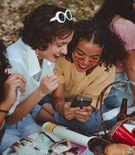 teens smiling at a cell phone