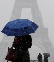 person holding an umbrella in front of the Eiffel Tower
