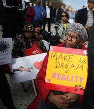 person holding a sign that says make his dream a reality