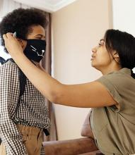 mother helping child put mask on