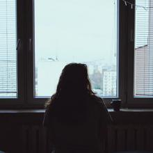 silhouette of a woman looking out a window