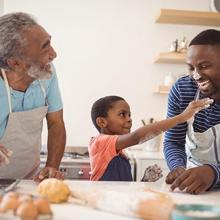father, grandfather, and child baking together in a kitchen