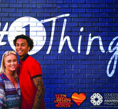teen couple in front of blue brick wall with #1Thing logo